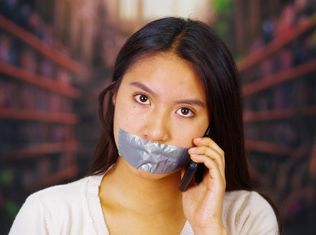 facing on camera: Young brunette woman wearing white sweater gagged with duct tape covering mouth, facing camera, hostage concept. Stock Photo