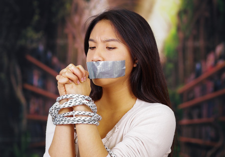 Young brunette woman wearing white sweater tied up with rope around wrists and duct tape covering mouth, facing camera, hostage concept.