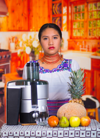blender: Charming young woman in traditional andean dress standing inside kitchen posing in front of juice maker, healthy lifestyle concept.