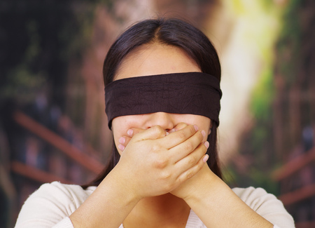 Young brunette woman wearing white sweater, blindfolded with black textile, covering mouth using hands, facing camera, hostage concept.