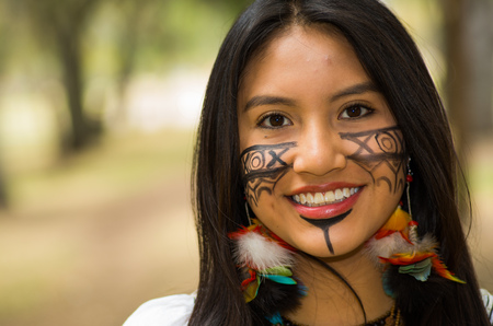 Headshot beautiful Amazonian woman, indigenous facial paint and earrings with colorful feathers, posing happily for camera in park environment, forest background.