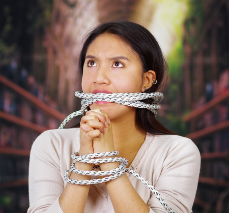 Young brunette woman wearing white sweater tied up with rope around wrists and gagged mouth, facing camera, hostage concept. Stock Photo