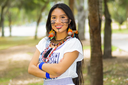 Beautiful Amazonian woman with indigenous facial paint and white traditional dress posing happily for camera in park environment, forest background.