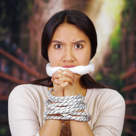Young brunette woman wearing white sweater tied up with rope around wrists and covering mouth, facing camera, hostage concept.