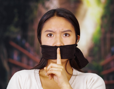Young brunette woman wearing white sweater gagged with black rope, holding up finger across mouth region, interacting silence, facing camera, hostage concept.