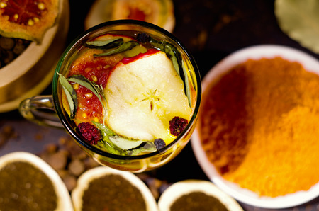 mideast: Transparent cup of infusion tea with colorful herbal selection inside, beautiful arrangement, teas and herbs concept. Stock Photo