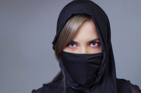 Headshot samurai woman dressed in black with matching veil covering face, facing camera, ninja concept. Stock Photo