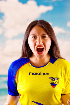 QUITO, ECUADOR -8 OCTOBER, 2016: Young ecuadorian woman wearing official Marathon football shirt standing facing camera, very engaged body language watching game with great enthusiasm, blue sky and clouds background.