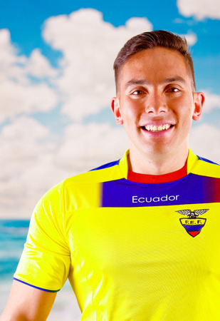 enthusiasm: QUITO, ECUADOR -8 OCTOBER, 2016: Young ecuadorian man wearing official Marathon football shirt standing facing camera, very engaged body language watching game with great enthusiasm, blue sky and clouds background.