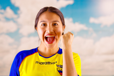 enthusiasm: QUITO, ECUADOR -8 OCTOBER, 2016: Young ecuadorian woman wearing official Marathon football shirt standing facing camera, very engaged body language watching game with great enthusiasm, blue sky and clouds background.