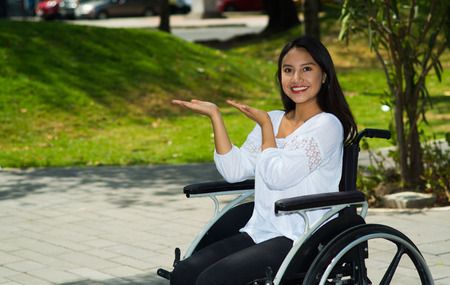 Young brunette woman sitting in wheelchair smiling with positive attitude, outdoors environment, physical recovery concept Stock Photo