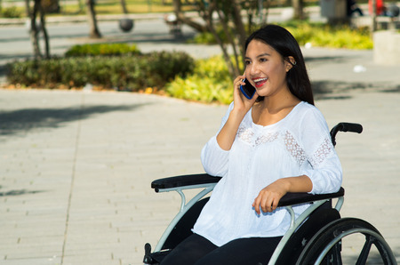 Young brunette woman sitting in wheelchair smiling with positive attitude, using mobile phone, outdoors environment, physical recovery concept Stock Photo