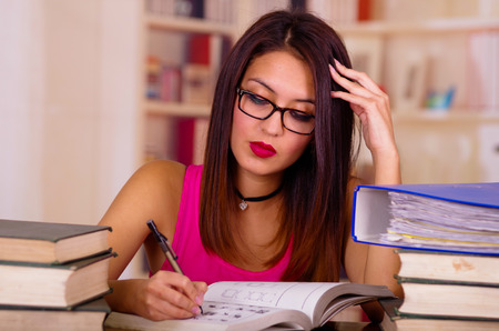 Young brunette woman wearing pink top sitting by desk with stack of books placed on it, resting head onto hand, tired facial expression, student concept.
