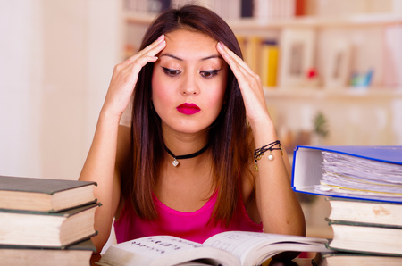 Young brunette woman wearing pink top sitting by desk with stack of books placed on it, holding hands onto head, tired facial expression and bodu language, student concept.