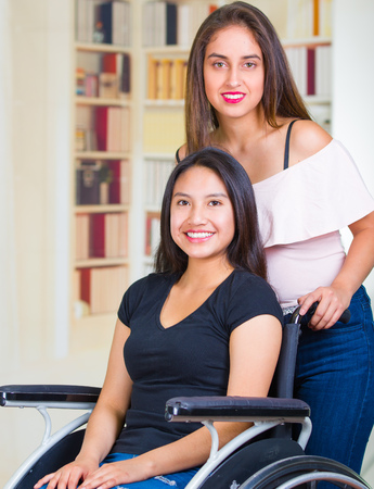 Young woman sitting in wheelchair with assistant standing next to her, both smiling happily showing positive attitude, physical recovery concept.