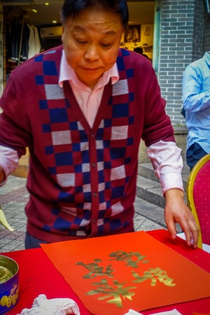 SHENZEN, CHINA - 29 JANUARY, 2017: Man painting on red decorative banner with golden letters, preparing for chinese new year