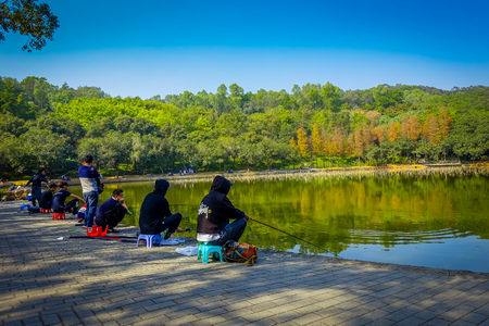 SHENZEN, CHINA - 29 JANUARY, 2017: Inside Lian Hua Shan park, large recreational area, people sitting while fishing in water lake sorrounded by trees, beautiful blue sky,