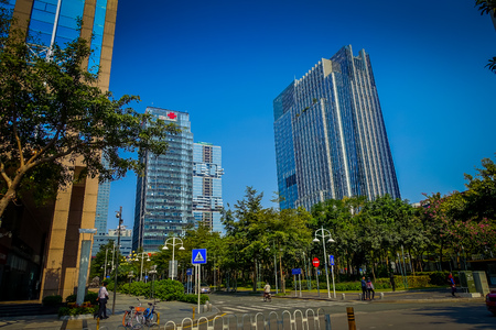SHENZEN, CHINA - 29 JANUARY, 2017: Inner city streets and sorroundings, beautiful mix of green trees combined with buildings, modern architecture, light traffic, totally blue skies