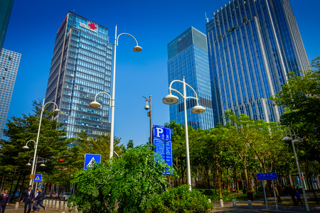 shenzhen: SHENZEN, CHINA - 29 JANUARY, 2017: Inner city streets and sorroundings, beautiful mix of green trees combined with buildings, modern architecture, light traffic, totally blue skies