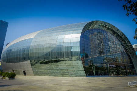 SHENZEN, CHINA - 29 JANUARY, 2017: Inner city streets and sorroundings of Nan Shan neighborhood, spectacular cultural arts building covered in shiny metal surface, totally blue skies