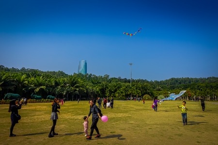 SHENZEN, CHINA - 29 JANUARY, 2017: Inside Lian Hua Shan park, large recreational area, people running on grass playing with kite, beautiful blue sky and tall building in background above trees