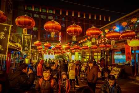 BEIJING, CHINA - 29 JANUARY, 2017: People walking around charming streets with small restaurants, traditional architecture and decorations, local Donghuamen food market concept.
