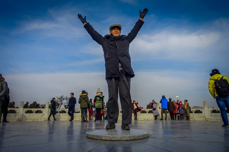 BEIJING, CHINA - 29 JANUARY, 2017: Tourist standing on flat stone inside temple of heaven compund, an imperial complex with various religious buildings located in southeastern central city area, nice blue sky.