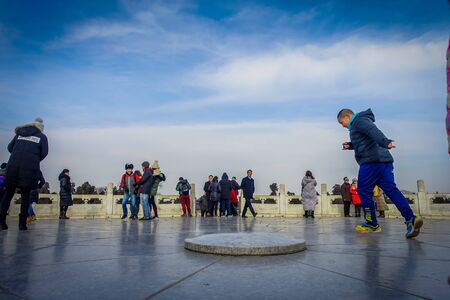 BEIJING, CHINA - 29 JANUARY, 2017: Tourist standing on flat stone inside temple of heaven compund, an imperial complex with various religious buildings located in southeastern central city area, nice blue sky