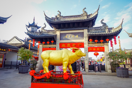 CHONGYUANG TEMPLE, CHINA: Golden bull statue standing in front of beautiful temple building