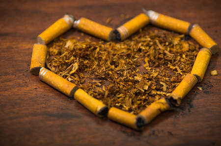 Cigarette butts shaped into a heart lying on wooden surface, tobacco spread around middle, seen from above