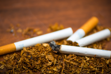 Closeup cigarettes and tobacco lying around on wooden surface, anti smoking concept