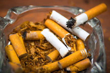 Cigarettes and tobacco lying inside and around glass ash tray on wooden surface, seen from above, anti smoking concept