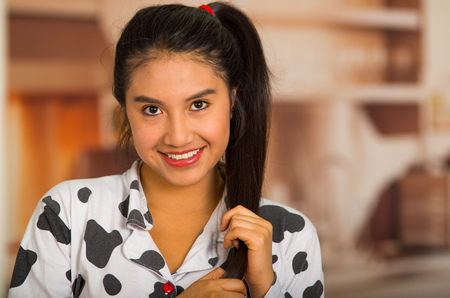 pijama: Young brunette woman posing in pyjamas, holding hair and smiling to camera Foto de archivo