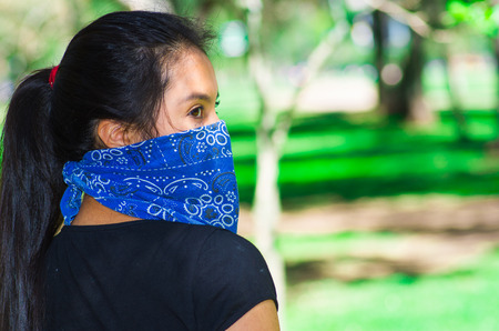 Young brunette woman wearing blue bandana covering half of face, interacting outdoors for camera, activist protest concept