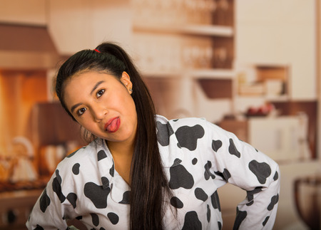 Young brunette woman posing in pyjamas, interacting with camera showing tongue and smiling Stock Photo