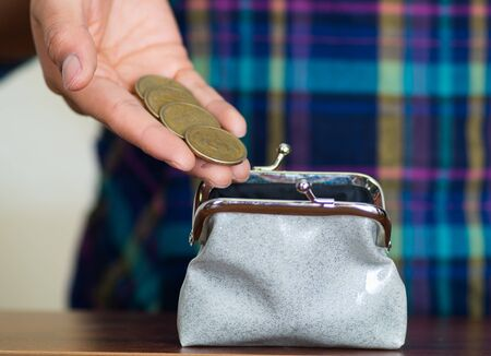 woman's hands: Womans hands facing camera, placing coins into small grey wallet Stock Photo