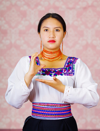 Young woman wearing traditional andean dress, facing camera doing sign language word for school Stock Photo