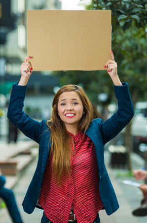 Young woman wearing casual clothes standing outdoors holding up cardboard poster, protesting concept