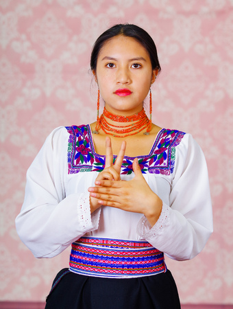 Young woman wearing traditional andean dress, facing camera doing sign language word for laugh
