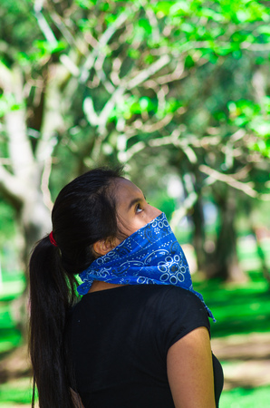 activism: Young brunette woman wearing blue bandana covering half of face, interacting outdoors for camera, activist protest concept