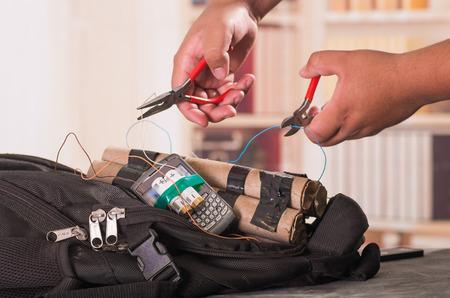 Close-up shot van handen snijden draden met tang van een geïmproviseerde explosieve apparaat bom Stockfoto