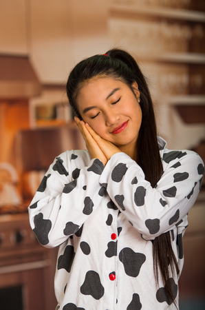 Young brunette woman posing in pyjamas, interacting sleeping with eyes closed using hands and smiling to camera