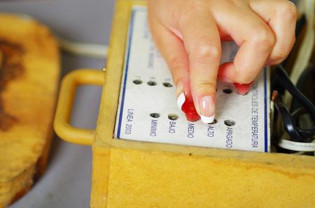 woodburner: Close up shot of hands adjusting the temperature of pyrography woodburner box