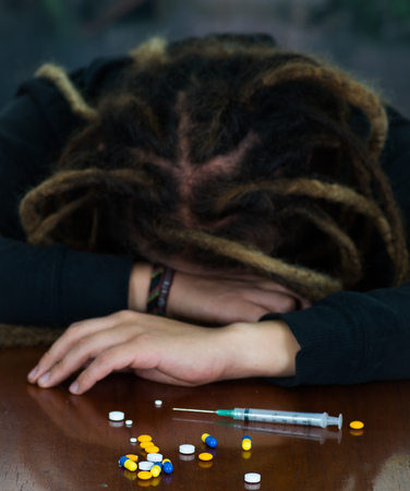 Man lying over table with dopey facial expression, colorful pills and syringe lying around desk, drug addiction concept Stock Photo - 75140254