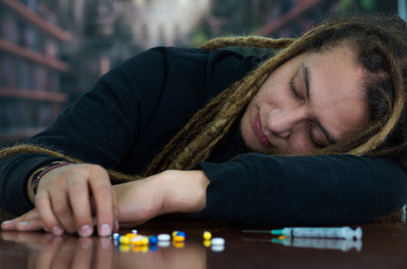 Man lying over table with dopey facial expression, colorful pills and syringe lying around desk, drug addiction concept Stock Photo - 75109194