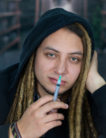 Man holding up syringe to camera with dopey facial expression, resting head on hand, drug addiction concept Stock Photo