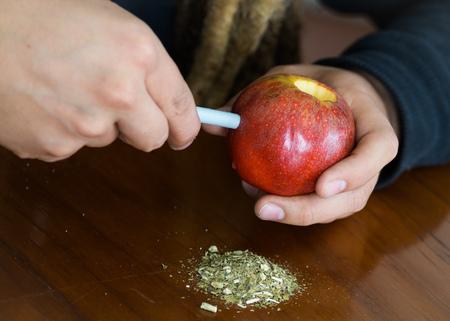Man creating an apple bong using knife and a plastic tube, drug addiction concept, marijuana lying on table