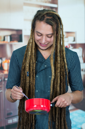 youth crime: Man with dreads and hippie look posing for camera holding red cooking pot, smiling happily, vegetarian concept