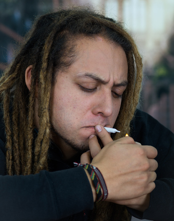 Man sitting down holding small joint to lips tring to light up, drug addiction concept