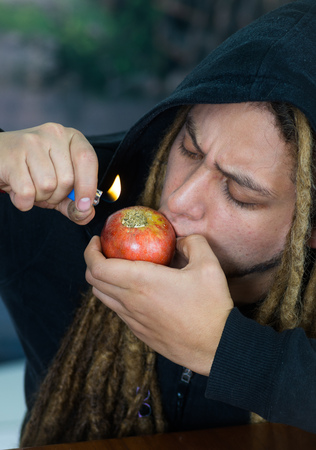 youth crime: Man smoking from homemade apple bong, drug addiction concept